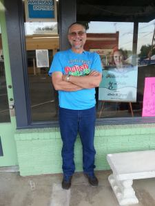 The Man in front of the store that hosted us. You can see my sign in the window.